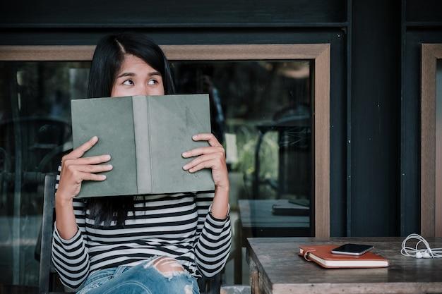 Frau, die ein buch liest und ihr gesicht bedeckt
