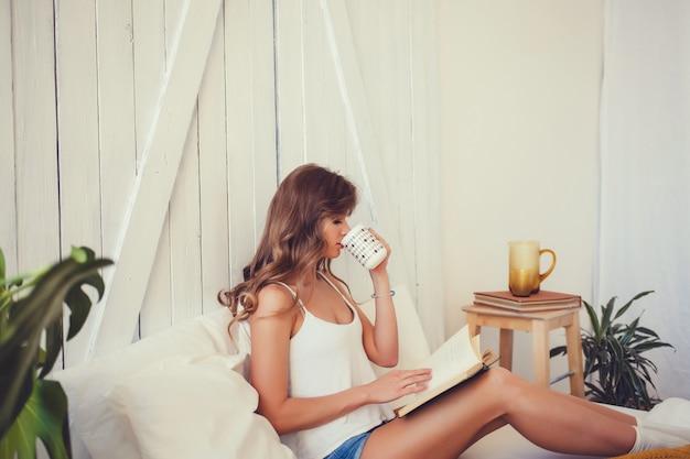 Frau, die ein buch liest und tee trinkt