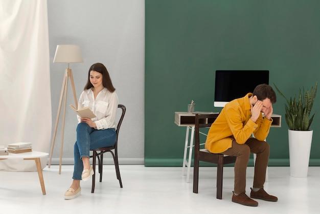 Frau, die ein buch liest, während mann gestresst ist