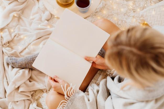 Frau, die ein buch liest, während sie die winterferien genießt