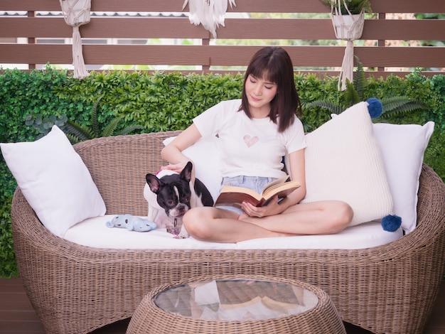 Frau, die ein buch mit einem hund auf dem sofa lesend sitzt