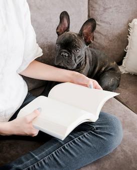 Frau, die ein buch mit ihrem welpen liest