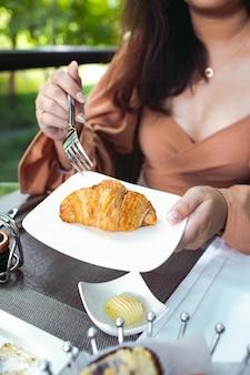 Frau, die ein croissant zum frühstück hat