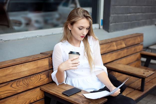 Frau, die ein dokument beim sitzen in einem café, einen morgentasse kaffee genießend, großaufnahme ihrer hände liest.