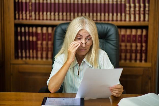 Frau, die ein dokument in ihrem studiobüro liest