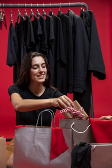 Frau, die ein eingewickeltes geschenk in eine einkaufstasche einsetzt