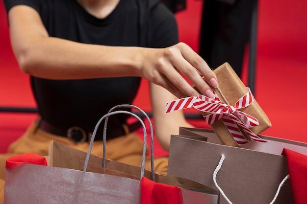 Frau, die ein eingewickeltes geschenk in eine einkaufstaschennahaufnahme einsetzt