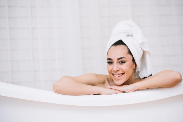 Frau, die ein entspannendes bad in einem badekurort nimmt