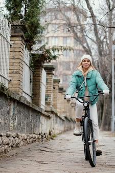 Frau, die ein fahrrad auf dem bürgersteig reitet