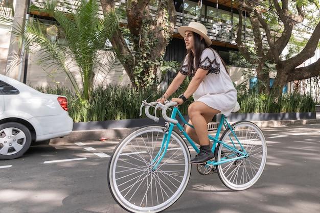Frau, die ein fahrrad auf der straße mit bäumen an den seiten fährt, trägt weißes kleid und hut