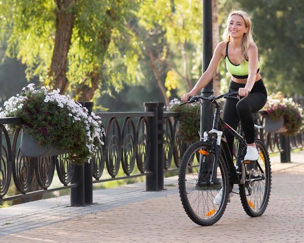 Frau, die ein fahrrad durch natur umgeben reitet