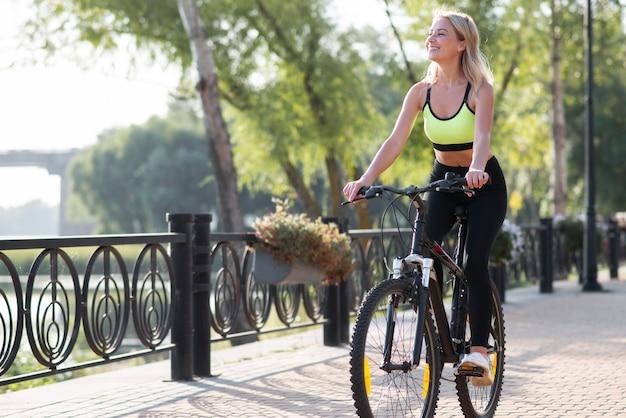 Frau, die ein fahrrad im park reitet