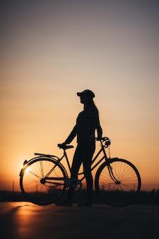 Frau, die ein fahrrad in der stadt während des sonnenuntergangs reitet