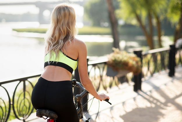 Frau, die ein fahrrad über dem schulterschuss reitet Premium Fotos