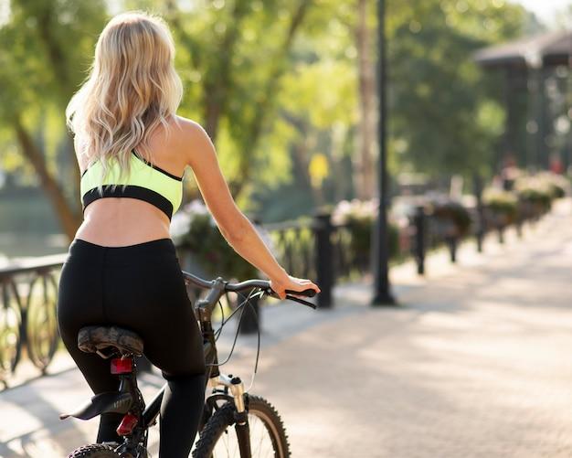 Frau, die ein fahrrad von hinten schuss reitet Premium Fotos