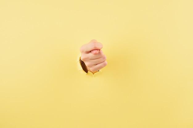 Frau, die ein feigenzeichen auf gelb zeigt