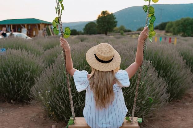 Frau, die ein feld des lavendels beobachtet