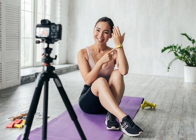 Frau, die ein fitnesstraining für einen neuen vlog zeigt