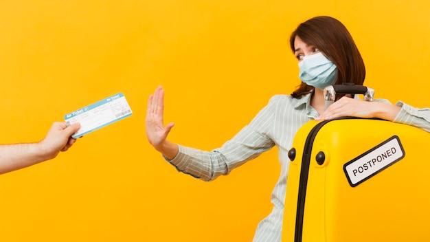Frau, die ein flugticket ablehnt, während sie e medizinische maske trägt