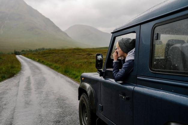 Frau, die ein foto aus dem autofenster macht