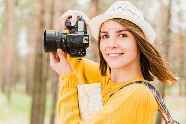 Frau, die ein foto beim gegenüberstellen der kamera macht