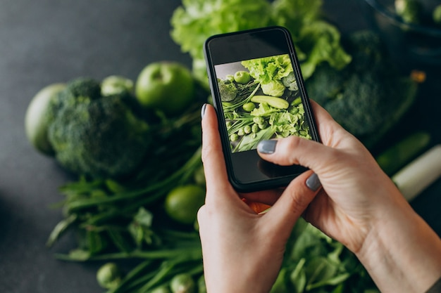 Frau, die ein foto des grünen gemüses auf dem tisch macht