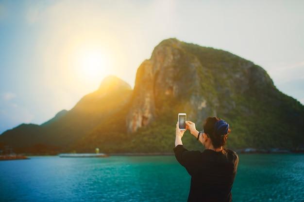 Frau, die ein foto des sonnenaufgangs und der seeküste macht