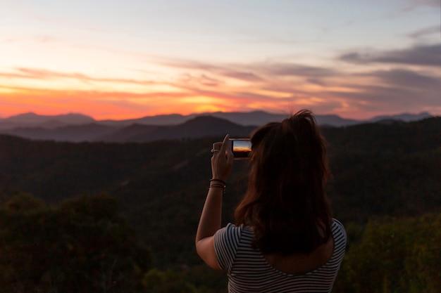 Frau, die ein foto einer schönen naturlandschaft macht