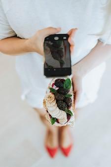 Frau, die ein foto eines toasts mit brombeermarmelade und frischkäse des strengen vegetariers macht