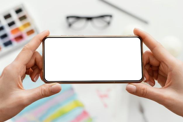 Frau, die ein foto ihrer kunst mit ihrem telefon macht