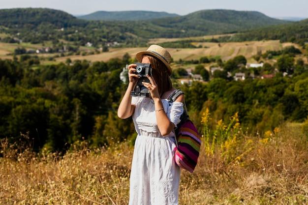 Frau, die ein foto macht und ihren rucksack trägt