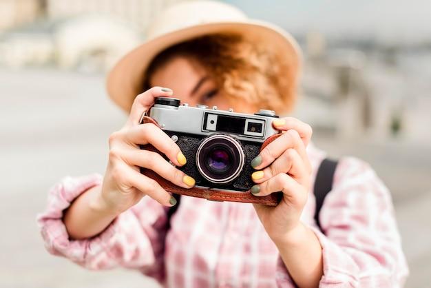 Frau, die ein foto mit einer kamera während des reisens macht