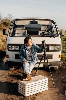 Frau, die ein foto mit einer retro-kamera macht