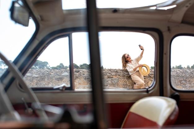Frau, die ein foto mit handy neben retro-auto auf der straße macht