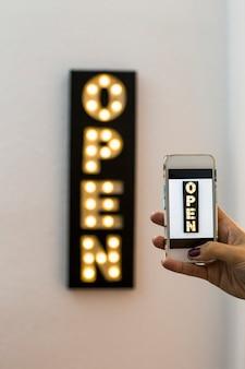 Frau, die ein foto mit handy zu einer geschäftsdekoration des neonlichtgeschäfts des offenen zeichens nimmt. glühbirne. vertikale ansicht