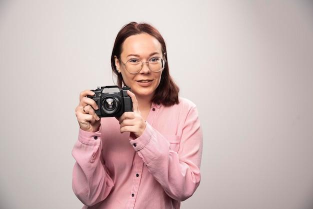 Frau, die ein foto mit kamera auf weiß macht. foto in hoher qualität