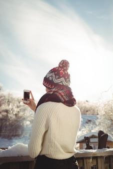 Frau, die ein foto unter verwendung des mobiltelefons am skigebiet nimmt