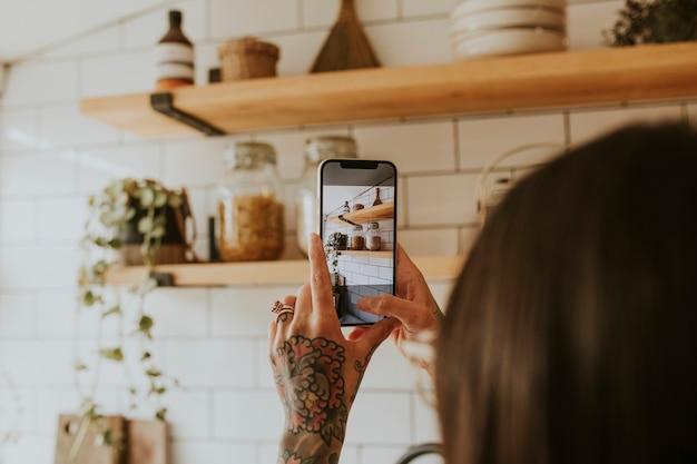 Frau, die ein foto von der wohnkultur der küche macht