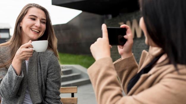 Frau, die ein foto von ihrem freund hält, der eine tasse kaffee hält