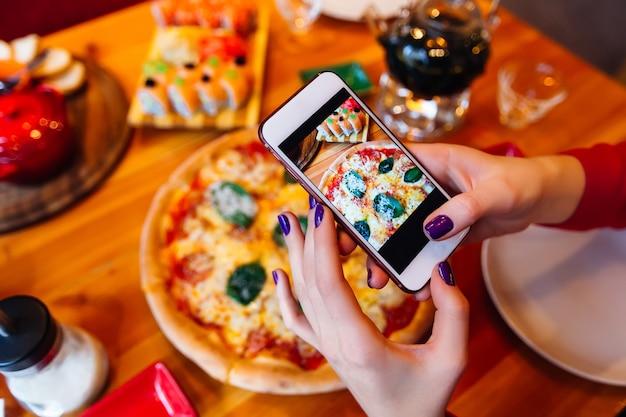 Frau, die ein foto von pizza und zutaten mit smartphone macht