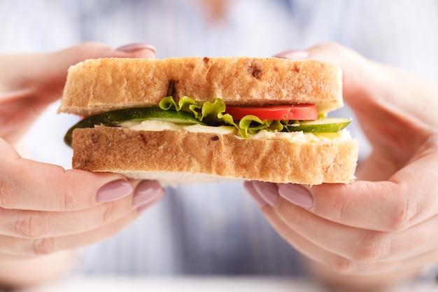 Frau, die ein frühstücks-sandwich isst und kaffee trinkt, während sie mit einem laptop arbeitet