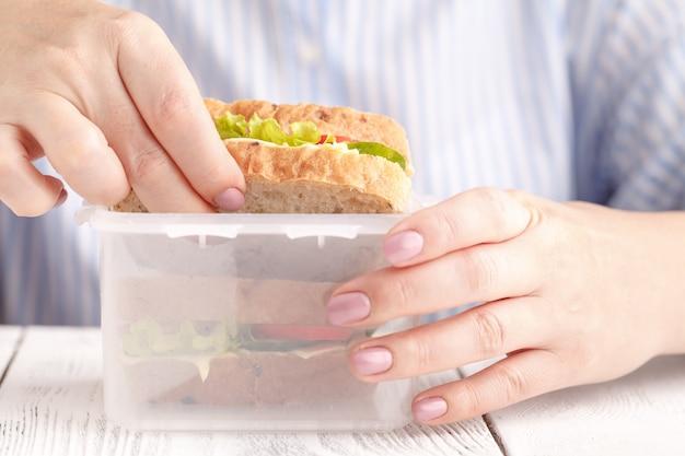 Frau, die ein frühstücks-sandwich isst und kaffee während der arbeit trinkt