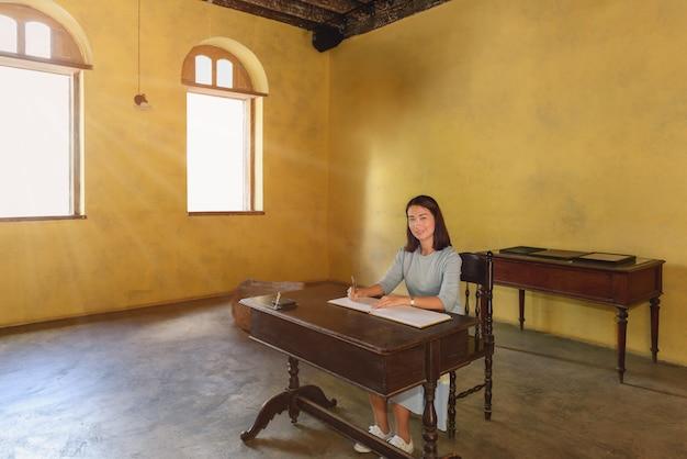 Frau, die ein gästebuch mit einem stift unterzeichnet