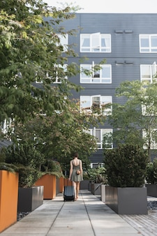 Frau, die ein gepäck im städtischen park trägt