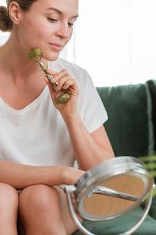 Frau, die ein gerät zur selbstpflege der gesichtsmassage verwendet
