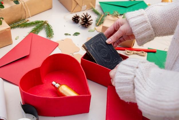 Frau, die ein geschenk für ein weihnachten auf einer tabelle einwickelt