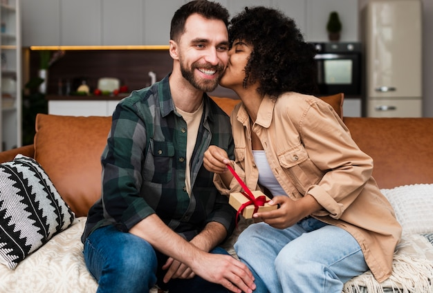 Frau, die ein geschenk hält und einen mann küsst