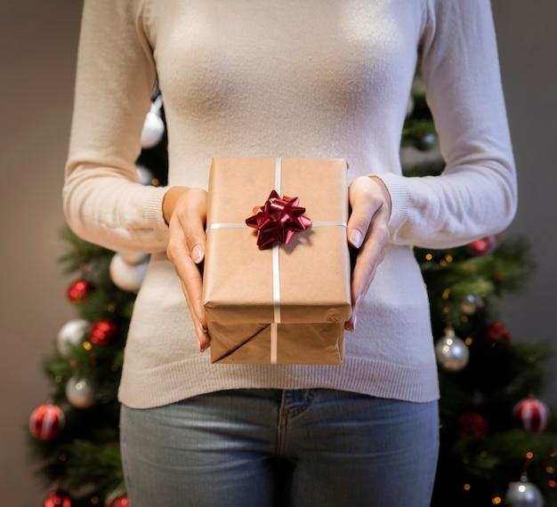 Frau, die ein geschenk in ihren händen hält
