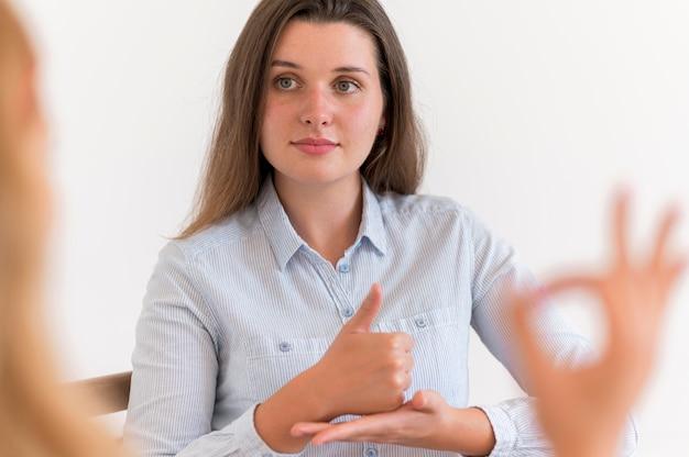 Frau, die ein gespräch mit jemandem unter verwendung der gebärdensprache hat