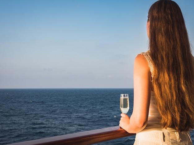 Frau, die ein glas auf der plattform anhält